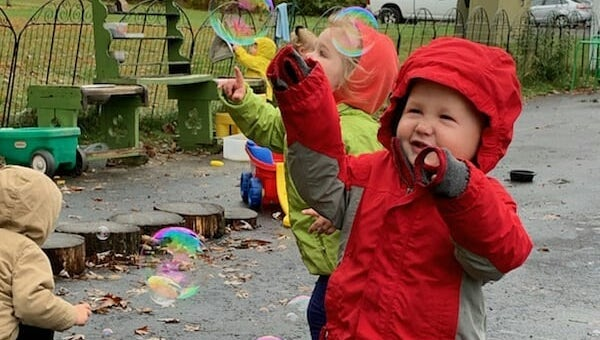 Toddlers outside with soap bubbles