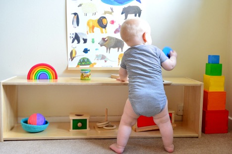 Baby using a low shelf to pull up to standing
